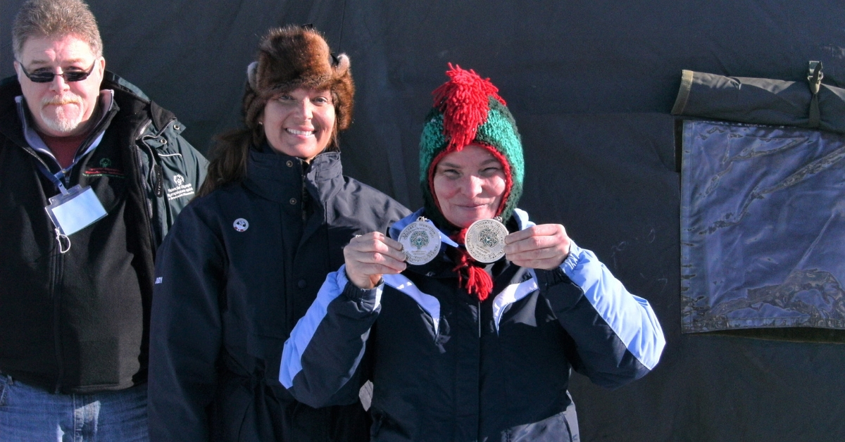 Patti Connors holds two medals at a Winter Games.