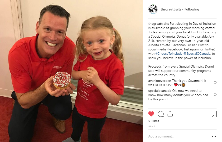 Mark Tewskbury holds a Special Olympics Donut with 6-year-old athlete Alma.