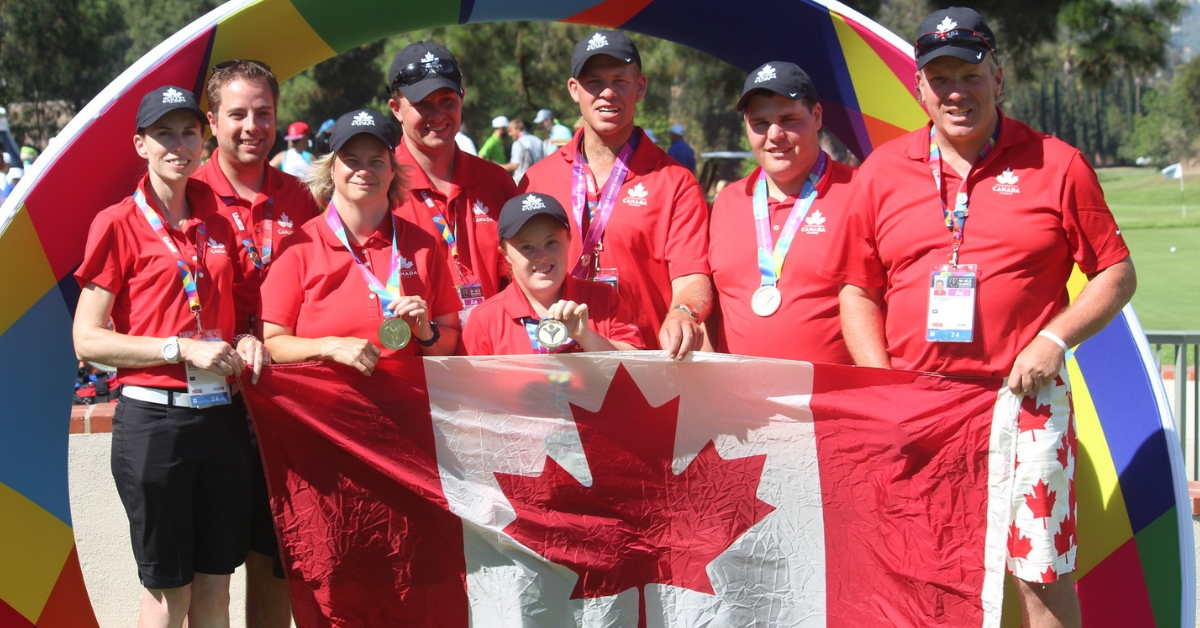 Mike McCarther (back left) holds up a Canadian flag with Special Olympics Team Canada 2015 golfers.