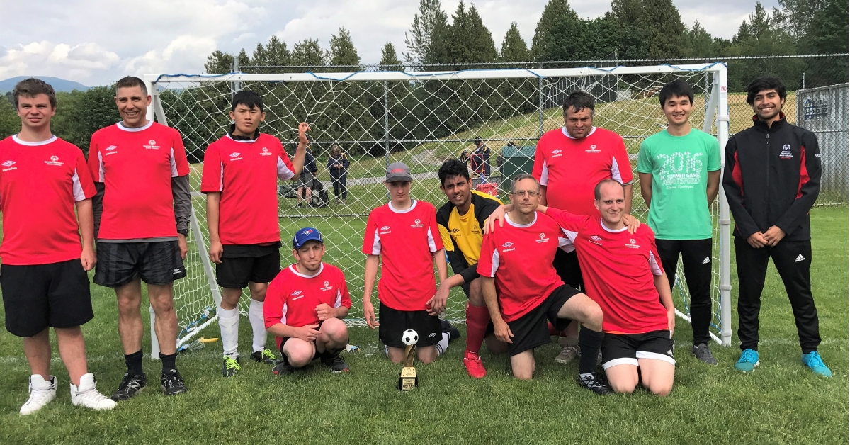 Roshan Gosal poses with his Special Olympics Abbotsford soccer team in front of a soccer net.