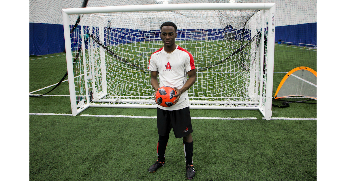 Eddie stands in front of a soccer net holding a soccer ball.