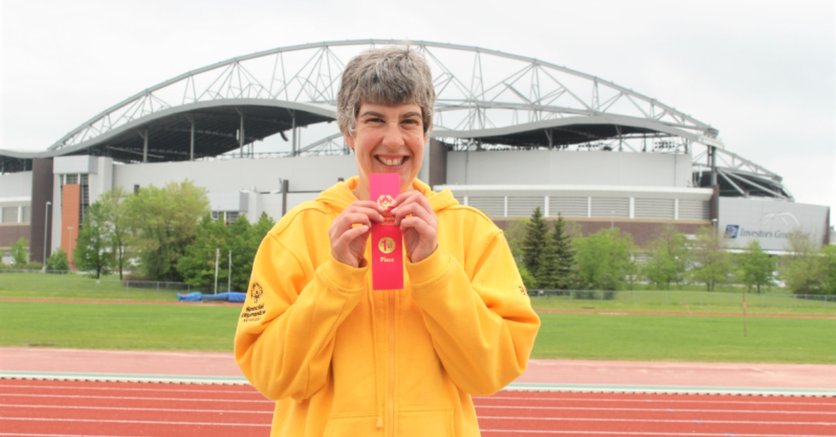 Special Olympics Manitoba athlete Brita Hall stands on a track holding up a first place ribbon.