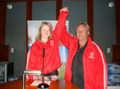 Darryl Sittler poses for a photo with a Special Olympics athlete while holding her arm up.