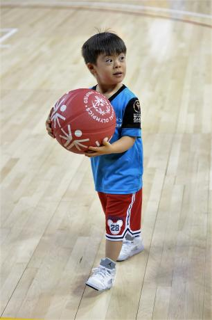 A young Special Olympics athlete holds a ball.