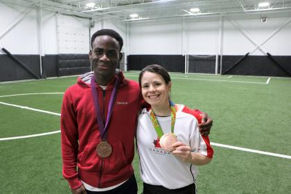 """Eddie and Canadian women's soccer player Diana Matheson hold her Olympic bronze medals."
