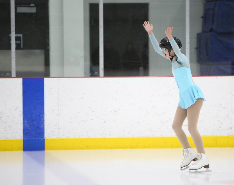Moriah on the ice with her arms up