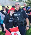 Mark Gugan, in his police uniform, poses for a photo with an athlete holding a Canadian flag.