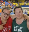 Two male Special Olympics athlete smile looking into the camera in front of a basketball court