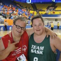 Two Special Olympics basketball players pose for a photo.