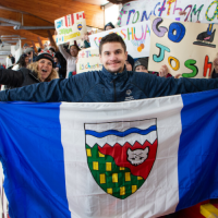 NWT speedskater Joshua Boudreau holds up the NWT flag in front of the Thunder Bay students whod rafted him, while holding support signs.