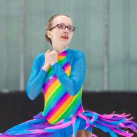 Jordyn Flamma spins on the ice in her rainbow dress.