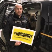 Const. Scott Edwards stands in front of a police car with his dog Chase in the front seat. Scott is holding a yellow sign that says #NoGoodWay