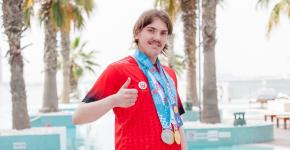 SO Team Canada swimmer Colby Kosteniuk gives the thumbs up while wearing his World Games medals.
