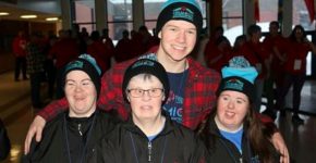 Logan Wilson poses for a photo with his arms around Special Olympics athletes.