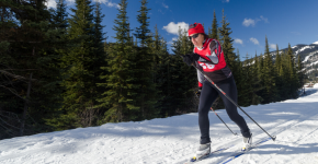 Tracey Melesko cross country skis in front of a tree line.