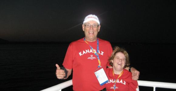 Gord Stewart poses on a boat with an athlete at World Games.