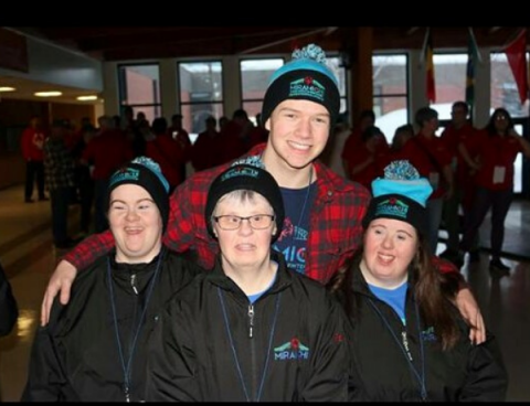 Logan poses for a photo with his arms around Special Olympics athletes.