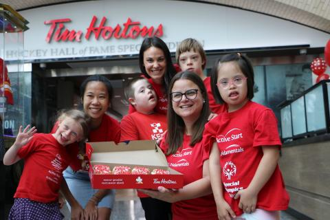 A group of young FUNdamentals athletes and their coaches stand in front of a Tim Hortons with donuts