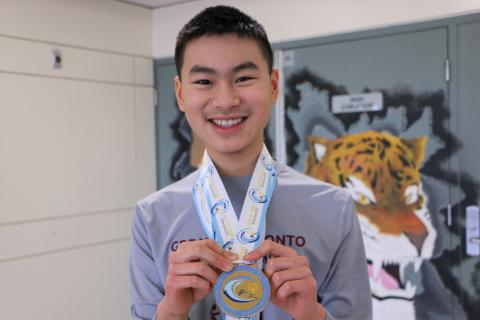 Ezekiel holds his gold medal, smiling at the camera.