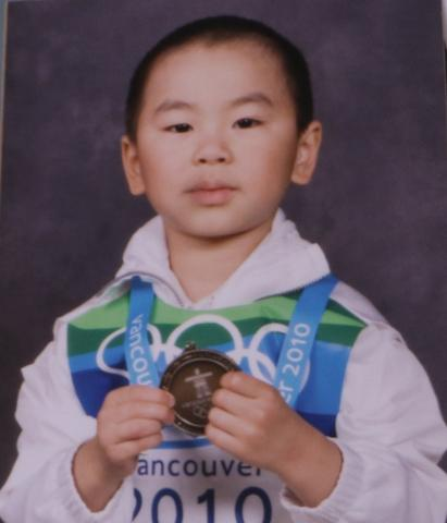 Ezekiel, four, holding a toy medal and wearing a Team Canada uniform.