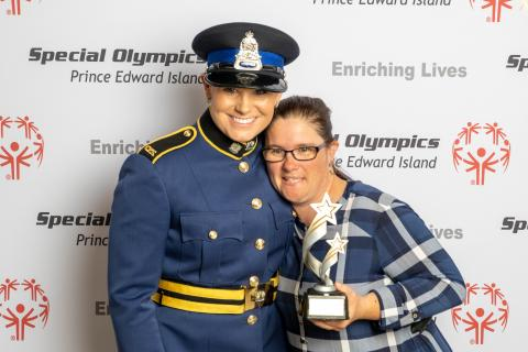 Kristi, dressed in her police uniform, poses for a photo with an athlete holding a trophy.