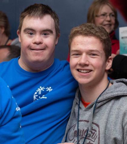 Logan smiles at the camera with a Special Olympics athlete