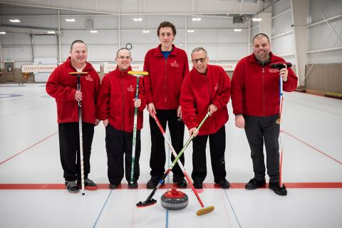 Adam poses for a photo with his curling team on the ice.