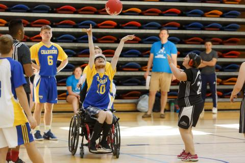 An athlete from a wheelchair tosses a basketball in the air